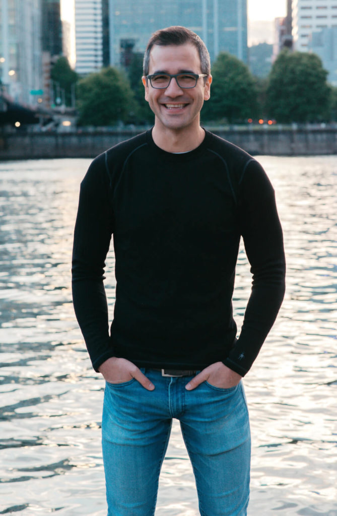 Ozan Varol standing by a body of water